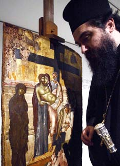 A Greek Orthodox priest prays in front of a 14th-century icon, Descent from the Cross. Julien Hammond says his years at a Ukrainian Catholic residential school gave him a greater sense of the diversity within the Catholic Church.