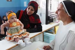 Sr. Nejmah Habash talks with Ronah Tebhoni and her two-month old daughter, Ranim, at a health clinic in Jordan run by the Dominican Sisters of St. Catherine of Siena.