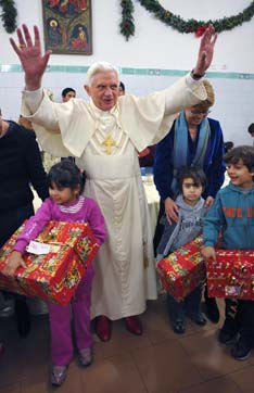 Last year, Pope Benedict waves after presenting gifts to children during a visit to a soup kitchen in Rome Dec. 27.