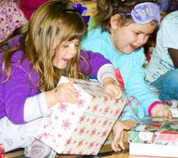 Katrina Gustin, left, and Isabella Corderio-Walesiak tear into shoeboxes filled with surprises.