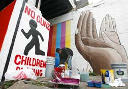 A man working on an anti-gun mural in Chicago illustrates the fact that the Vatican is pushing for strict controls on handguns.
