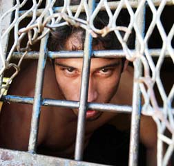 Church workers try to help inmates such as this man peering through a barred window at Tacumbu high security prison in Paraguay.