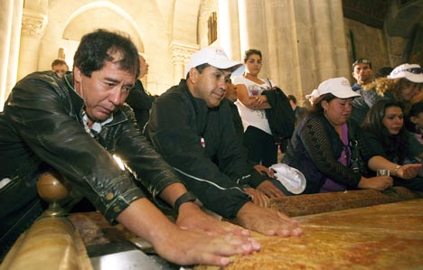 Chilean miners, who were trapped in a collapsed mine near Copiapo, Chile, for 69 days before being rescued in October, touch the Stone of Anointing in the Church of the Holy Sepulchre in Jerusalem's Old City Feb. 24.