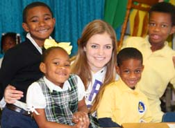 New Orleans children smile their appreciation of Brenna Haggarty's help during reading class.