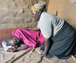 A home-based care worker prays for a man living with AIDS in Malawi, in this 2009 photo.