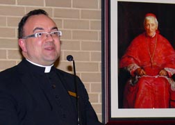 Fr. Stefano Penna, dean of Newman College, stands next to a painting of Blessed John Henry Newman.