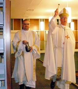 Assisted by Deacon Paul Croteau, Archbishop Richard Smith blesses the library at Newman Theological College March 8.