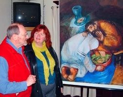 Rev. Paul Fachet and STM Campus Ministry team member Madeline Oliver discuss the 'washing of the feet' painting by German Catholic priest and artist Sieger Köder