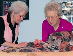 Marie Parent and Cécile Pahud carefully piece together material for a warm quilt
