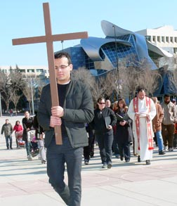 Seminarian Miguel Irizar carries the cross  through Winston Churchill Square in the Communion and Liberation Way of the Cross April 22.