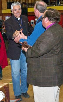 Catholic Bishop Murray Chatlain shakes hands with an Anglican prelate at a reconciliation ceremony in Inuvik.