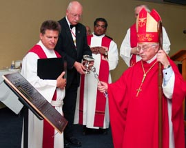 Calgary Bishop Fred Henry blesses a plaque at Fr. Michael J. McGivney Hall during a June 12 mass dedicating the building on the St. Mary's University College campus.