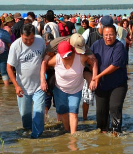 Shelia Mason, centre, gets help in carrying her legless husband Loren out of the lake.