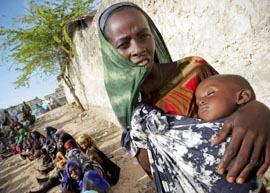 A woman holds her baby outside a tent serving as a medical clinic in Mogadishu, Somalia, July 16.
