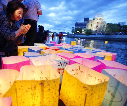 A woman prays after releasing a paper lantern on a river facing the gutted Atomic Bomb Dome Aug. 6, the 66th anniversary of the world's first atomic bombing. More than 75,000 people were killed in Hiroshima when the United States dropped the bomb near the end of the Second World War.