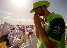 A volunteer prays during the World Youth Day closing Mass led by Pope Benedict XVI at Cuatro Vientos airfield in Madrid Aug. 21. 'The Lord loves you and calls you his friends,' the pope told the 1.5 million pilgrims attending the finale.