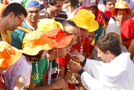 A priest distributes Communion to pilgrims during the closing Mass of World Youth Day in Madrid Aug. 21.