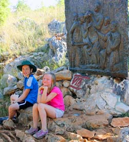 Luke and Madelyn pause in the shade of the Seventh Station of the Cross at Medjugorje.