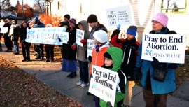 Local pro-lifers, adults and children alike, prayed and proclaimed their message across from Women's Health Options, an abortion clinic.