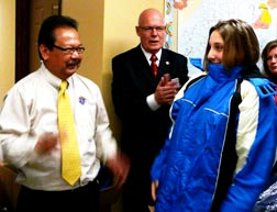 State Warden Vince Reyes presents a new winter coat to a young resident of Slave Lake while State Deputy Gary Johnson looks on.