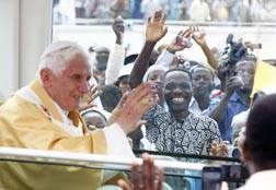 People cheer as Pope Benedict leaves in his popemobile after celebrating mass at the stadium in Cotonou, Benin, Nov. 20.