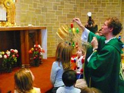 Fr. Dean Dowle incenses the Blessed Sacrament during Eucharistic Adoration for children.
