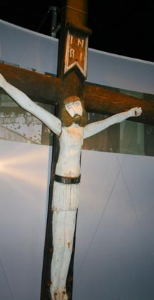 A large roadside crucifix from Quebec is hand-carved in a primitive style.