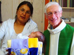 Father Rodrigue Vézina is shown with a woman and her child whom he baptized.