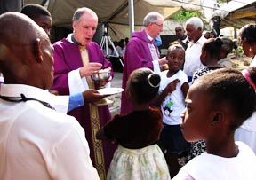 Archbishop Paul-André Durocher and Archbishop Richard Smith concelebrate a Mass in Port-au-Prince to assembled Haitians dressed in their Sunday best, despite their desperate poverty and the ongoing ravages of a catastrophic earthquake.