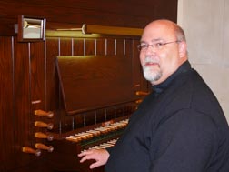 Fr. Shayne Craig sits next to the 30-year-old Casavant pipe organ installed in the chapel of St. Joseph Seminary in January.