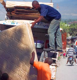 Residents of Petite Place Cazeau camp for Haitians displaced by the January 2010 earthquake load a truck with belongings in December as they move to a new permanent home.
