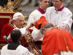 Pope Benedict presents a red biretta to Cardinal Thomas Collins at the Vatican Feb. 18.
