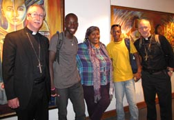 Archbishop Richard Smith, young Haitian artists and Archbishop Paul-André Durocher stand in front of paintings of the artists at the Musée du Panthéon national haïtien.