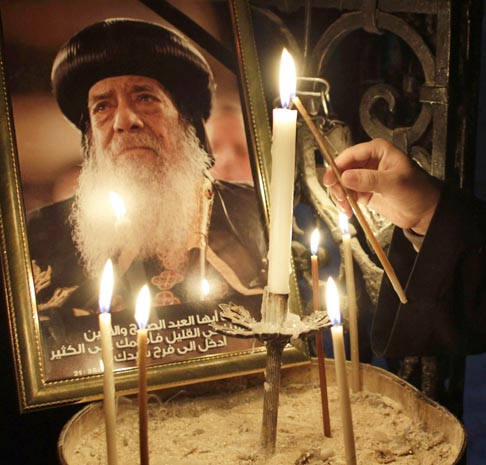 In Jerusalem's Church of the Holy Sepulcher March 18, a priest  lights a candle in front of a picture of Coptic Orthodox Pope Shenouda III of Alexandria, Egypt. Pope Shenouda, patriarch of the Coptic Orthodox Church for 41 years, died March 17 at age 88.