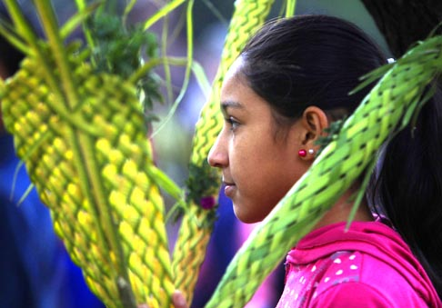 A young woman takes part in a Palm Sunday procession before Mass at the Catholic cathedral in Capiata, Paraguay, April 1. Also known as Passion Sunday, it commemorates Christ's triumphant entry into Jerusalem before his crucifixion.