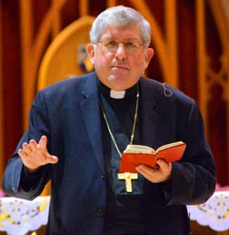 Cardinal Thomas Collins reads from a red Bible - because a Bible must be read.