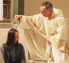 Tsara Davis is baptized by Fr. Pierre Leblond during St. Mary's Easter Vigil.