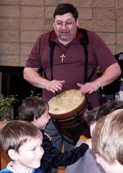 Br. Dan Dionne drums some happy beats for the Holy Childhood Association children.
