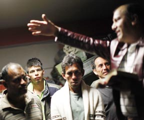 Men listen to an evangelical preacher during Christmas Eve at a migrants' shelter in Tultitlan on the outskirts of Mexico City last year.