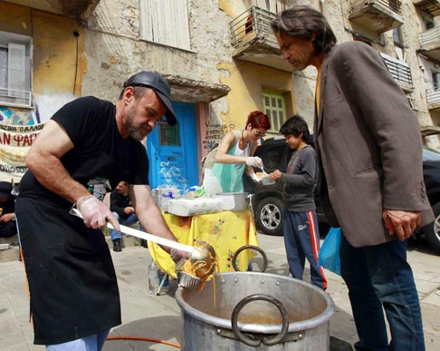 Constantinos Polychronopoulos, 47, an unemployed marketing specialist, distributes food portions at a soup kitchen for the poor in Athens, Greece, April 24.  Deep austerity measures being discussed by several European governments have led voters to oust incumbent officials, opening the door for less drastic approaches to rebuilding fragile economies.