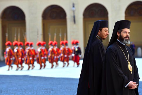 Bulgarian Orthodox priests stand in the Vatican's courtyard as Swiss Guards march behind them prior to Pope Benedict's private audience with Bulgaria's President Rosen Plevneliev May 24.