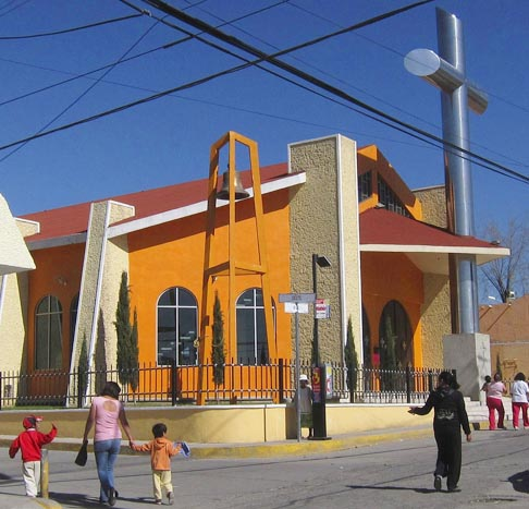 People walk past a chapel built by Los Zetas drug cartel founder Heriberto Lazcano in Pachuca, Mexico. The large orange Catholic chapel, with a towering cross, would be just another chapel if not for a bronze plaque announcing that it was donated by Lazcano, better known as the executioner.