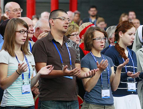 Young people pray the Lord's Prayer during a Mass for Canadian pilgrims at the International Eucharistic Congress in Dublin June 11. St. Boniface Archbishop Albert LeGatt celebrated the Mass.