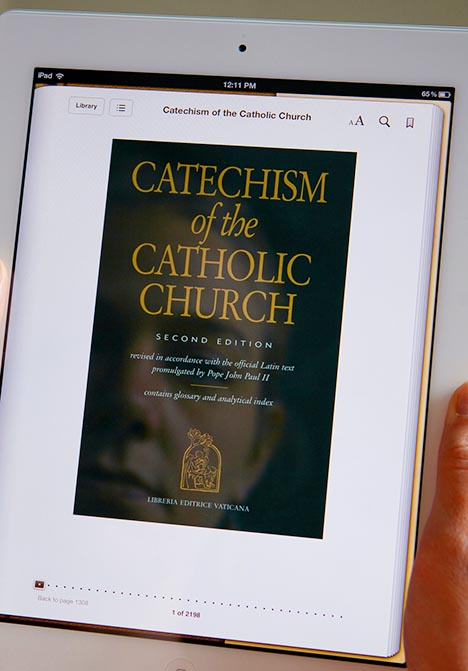 A woman displays the e-book version of the Catechism of the Catholic Church on an iPad. The e-book version, which has been available through iTunes, Amazon and the U.S. Conference of Catholic Bishops' online bookstore, can now be browsed and read for free on the USCCB website (www.usccb.org).