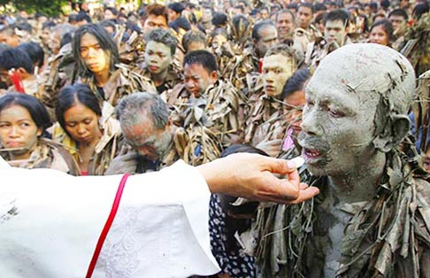 A worshipper covered with mud receives Communion during a Mass celebrating the feast of St. John the Baptist in the remote village of Bibiclat, north of Manila, Philippines, June 24. Hundreds of Catholics participated in the religious tradition, which has been held in the village annually since 1945.