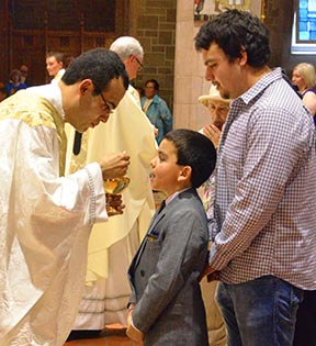 Irizar offers First Communion to his brother Alvaro.