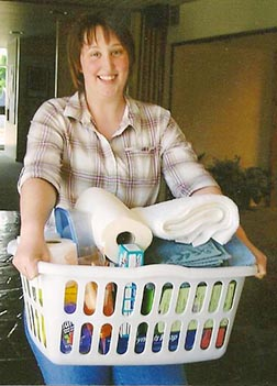 CWL member Karen Bernes holds a laundry basket of items for a woman leaving the women's shelter.