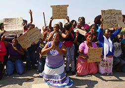 Women protest outside the Lonmin platinum mine Aug. 17, the day after South African police opened fire on striking miners.