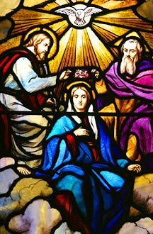 The coronation of the Blessed Virgin Mary is depicted in a stained-glass window.