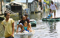 Residents use makeshift rafts to cross floodwaters near Manila Aug. 11. The Office of Civil Defence said the floods left at least 66 people dead and affected nearly three million people in Manila and nearby provinces.